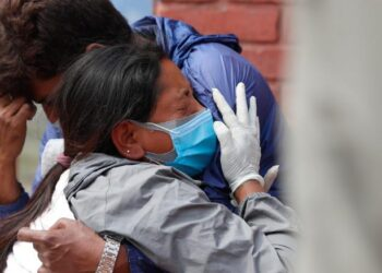 Relatives of a person who died of COVID-19 mourn at a crematorium in Kathmandu, Nepal, Friday, April 30, 2021. An infection surge in Nepal has prompted the government to impose new lockdowns in major cities and towns, restricting the movement of people and vehicles and shuttering markets, offices and schools. (AP Photo/Niranjan Shrestha)